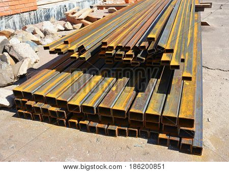 Rust steel channel bunch on house construction site outdoors.