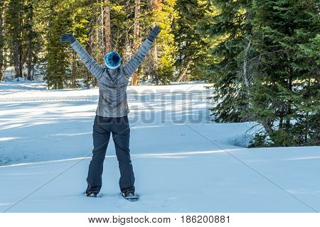 Power Posing in Snowy Utah Forest While Wearing Snow Shoes