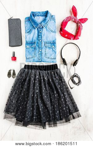 Top view of female clothes. A collage of woman tull skirt denim shirt and accessories. Fashionable urban outfit.