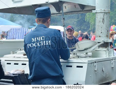 PYATIGORSK, RUSSIA - MAY 09, 2017: The employee of the Ministry of Emergency Situations distributes porridge and food Movable kitchen