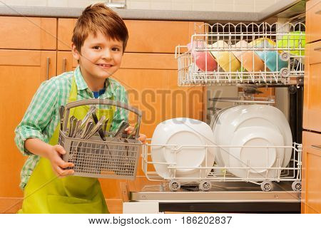 Portrait of happy kid boy pulling out a basket with clean cutlery of the dishwasher in the kitchen