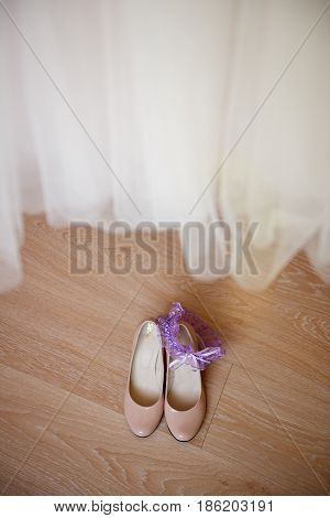 Bride's Shoes Under A Wedding Dress