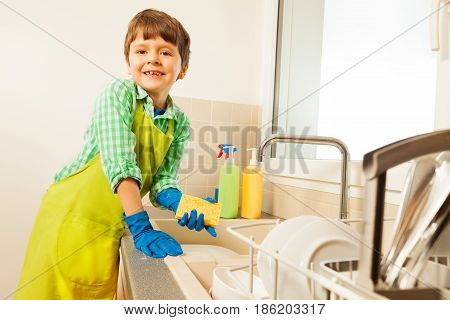 Happy kid boy in rubber gloves standing next to the sink and holding sponge