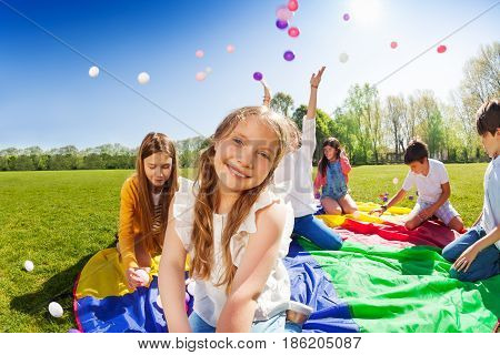 Close-up portrait of smiling fair-haired girl, sitting on rainbow parachute during the game with friends in the park