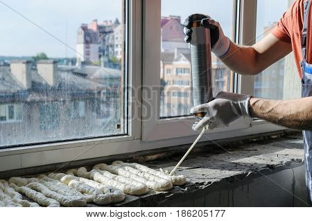 Worker is using a polyurethane foam for installation of window sill.