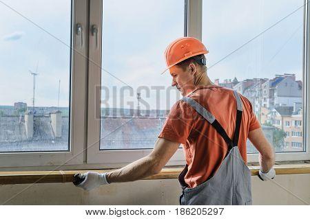 Worker is installing a window sill on a polyurethane foam.