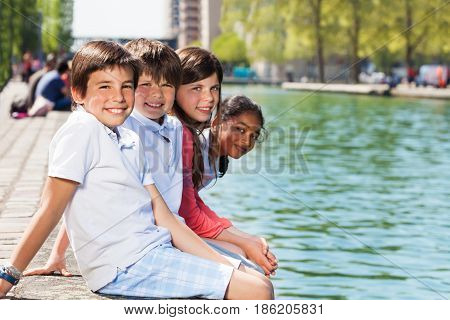 Happy friends, ten years old boys and girls, sitting on the bank of the river, enjoying summer holidays