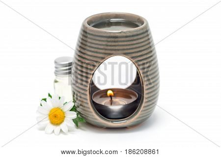 Aroma lamp with chamomile essential oil glass bottle with oil and fresh flowers on background isolated on white