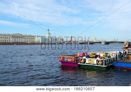 SAINT PETERSBURG RUSSIA - MAY 1 2017: Unknown people are waiting on pleasure boats for water excursion on Neva River. View of Kunstkamera Spit of Vasilyevsky Island Peter and Paul Fortress and Palace Bridge