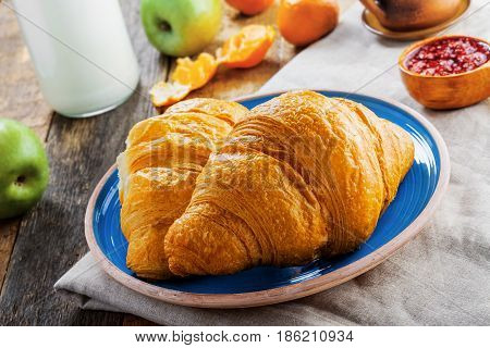 Classic French food for healthy breakfast. Plate of fresh croissants fruit jam and milk on a rustic wooden table.