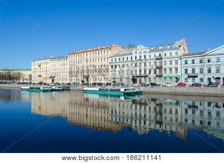 SAINT PETERSBURG RUSSIA - MAY 2 2017: Beautiful view of embankment of Fontanka River with reflections of buildings in water. Building of St. Petersburg State University of Ways of Communications of Emperor Alexander I