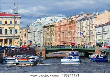 SAINT PETERSBURG RUSSIA - MAY 3 2017: Excursion boats on Moika River near Green Bridge in St. Petersburg. Unidentified tourists are visiting sights during walk along rivers and canals of city