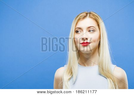 Portrait of Nice-looking Blonde with Long Hair Looking at Something in Studio on Blue Background.