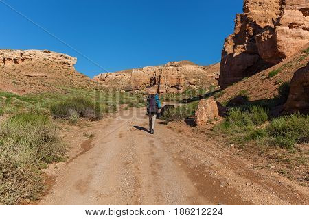 Hiker with backpack walking along the road to Charyn Canyon visit to Kazakhstan sights of Kazakhstan