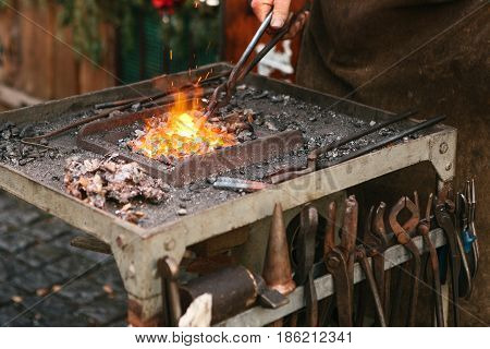 Blacksmith working metal with a hammer on the anvil in the forge. Outdoors scene.