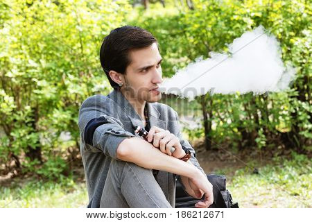 Thoughtful young businessman smokes a vape in a park in the spring afternoon
