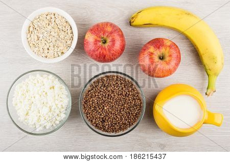 Milk cottage cheese buckwheat oatmeal and fruits on wooden table. Top view poster