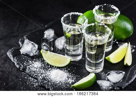 Mexican tequila gold in short glasses with salt, lime slices and ice on black background
