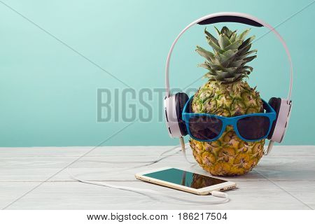 Pineapple with sunglasses headphones and smart phone on wooden table over mint background. Tropical summer vacation and beach party concept.