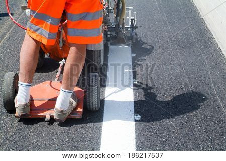Bissone Switzerland - 20 June 2011: Machine eject and worker on road and traffic sign painting