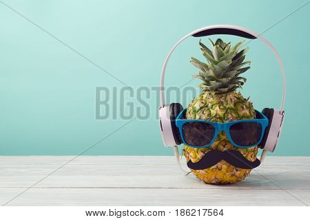 Pineapple with sunglasses and headphones on wooden table over mint background. Tropical summer vacation and beach party concept.