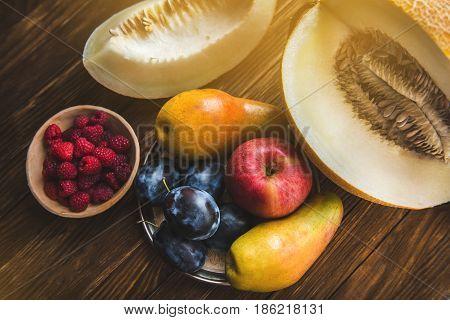 Assortment of fresh fruits and berries. Fruits plum apple pear. Berries red raspberries. Fruit bowl. Still life