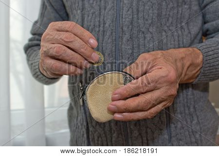 An Elderly Man In A Hand Holds A Coin And A Empty Wallet. The Concept Of Poverty In Retirement.