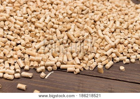 Wood Pellets Spill Out Of The Packaging On Wooden Background . Biofuels. The Cat Litter .
