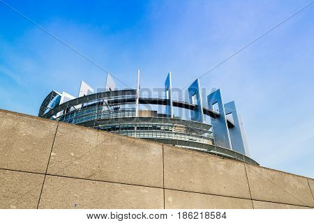 STRASBOURG FRANCE - MAR 31 2017: Official European Union flags - European Parliament building in Strasbourg France behind security stone wall