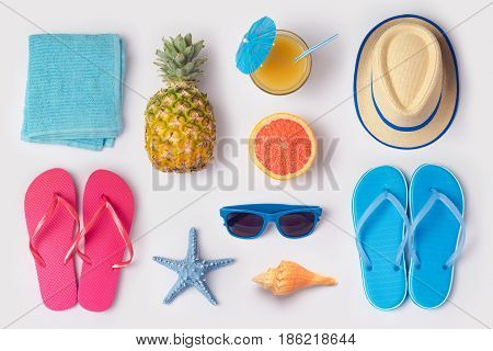 Tropical summer vacation concept with pineapple juice and flip flops organized on white background. View from above. Flat lay