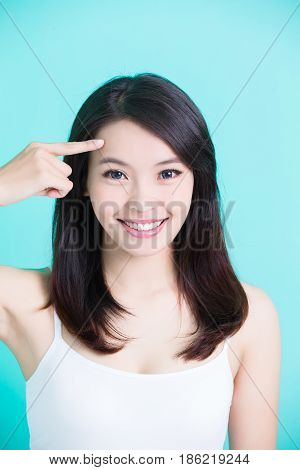 beauty skincare woman smile happily and touch her forehead on green background
