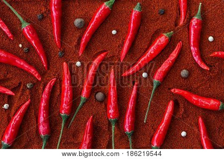 red hot chili peppers, popular spices concept - beautifully distributed red chili peppers on a brown background of ground dried pepper with round seeds of black pepper and juniper berries