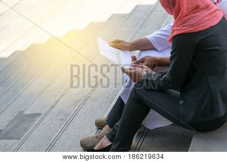Arab businessman and Businesswoman check graph on paper finance concept
