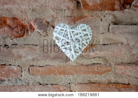 Heart made of white branches on the old brick wall background