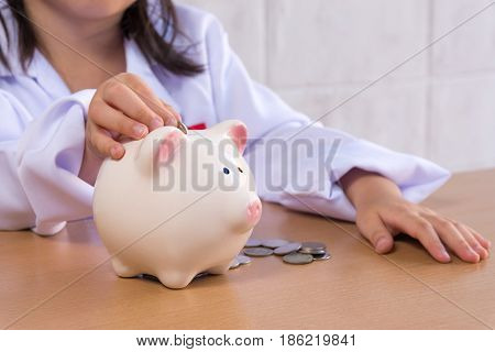 Asian girl playing as a doctor balance money in Piggy Bank