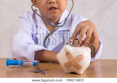 Asian boy playing as a doctor care Piggy Bank