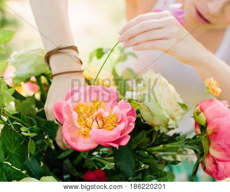 bouquet, holidays, people and floral arrangement concept - close up on hands of women designer making beautiful bouquet of purple peonies and white roses, young girl florist in white work with flower