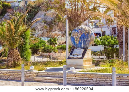 Rethymno Greece - May 3 2016: Monument with globe book and handshake in memorial Park along promenade Emmanouil Kefalogianni. Park at foot of fortress Fortezza Castle on hill Paleokastro. Crete