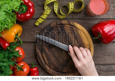 Female hands cutting vegetables at table, top view. On the table leaves of lettuce, pepper, a glass of tomato juice, a wooden board and a knife