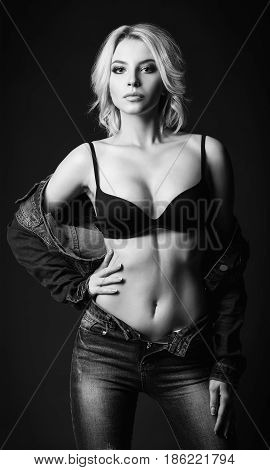 Studio fashion shot: a sensual beautiful young woman in denim and underwear. Black and white