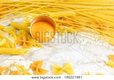 A closeup of an egg among various types of pasta, on a white marble table with flour and a place for text