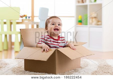 pretty baby infant boy sitting inside a box in new apartment
