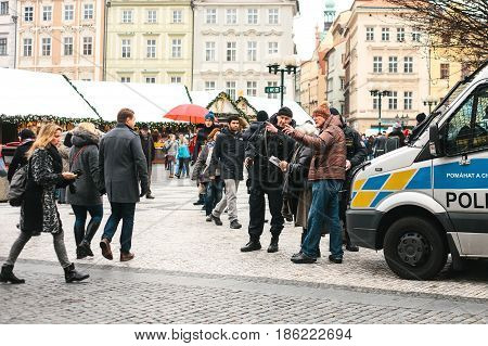Prague, Czech Republic - December 25, 2016: Czech policemen on a Christmas day help the tourist - show the desired place of attractions on the map. Respectful attitude to tourists from the authorities.