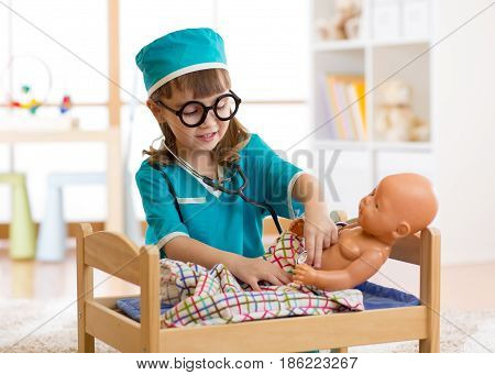 Child with clothes of doctor plays with doll