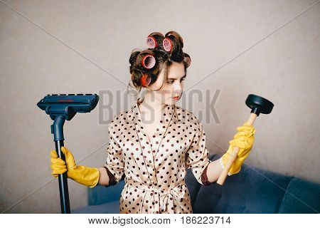 girl in a dressing gown with curls on her head curlers holds a plunger and a brush from a vacuum cleaner. The concept is better to clean the blockage in the sink and pipes.