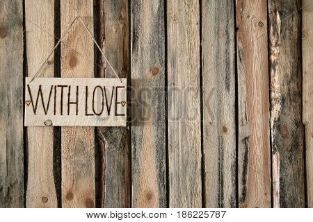 Plaque with the inscription WITH LOVE hangs to the left on the background of wooden wall. Horizontal photo