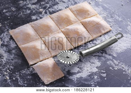Uncooked ravioli and cutter on table
