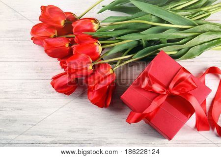 Bouquet of beautiful tulips and giftbox on light wooden background