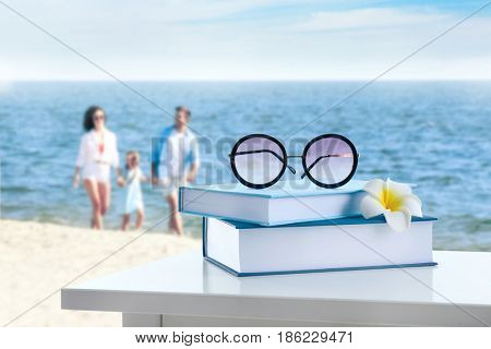 Reading during summer vacation. Books and sunglasses on landscape background
