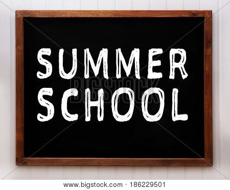 Blackboard with text SUMMER SCHOOL on wooden background
